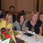 A group of guests pose with Barclay at their table for the photographer.