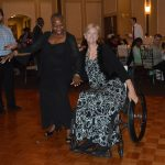 Guests take to the dance floor to enjoy the DJ and Music. One of the dancers is in a wheelchair.