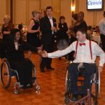 Guests take to the dance floor to enjoy the music. Two of the guests are in wheelchairs dancing.