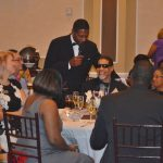 During the Pigskins & Bowties Gala, host Jay Jefferies roamed around to the different tables and stopped with Walton Options' own Brian who is seated at a table with multiple other guests dressed in their finest.