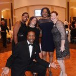 A group of Walton Options' staff post on the dance floor with Jay kneeling in front of them - all the ladies are smiling.