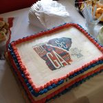 A celebration cake on a table with additional finger foods. The cake is white with red and blue trimming and the CSRA ADA25 logo in the middle of the cake in blue, red and white.