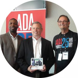 A group of three men stand in front of a roll-up ADA25 banner. The man in the middle is holding an award with a photo on it. All three men are looking towards the camera posed.