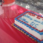 The ADA26 anniversary cake on the table next to the pink lemonade dispenser.