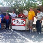 Walton Options staff celebrate with an ice cream from Bruster's Ice. One staff member is in a blue shirt with her back to the camera on the left, the ice cream cart is in the middle with two male guests standing to the right of it.
