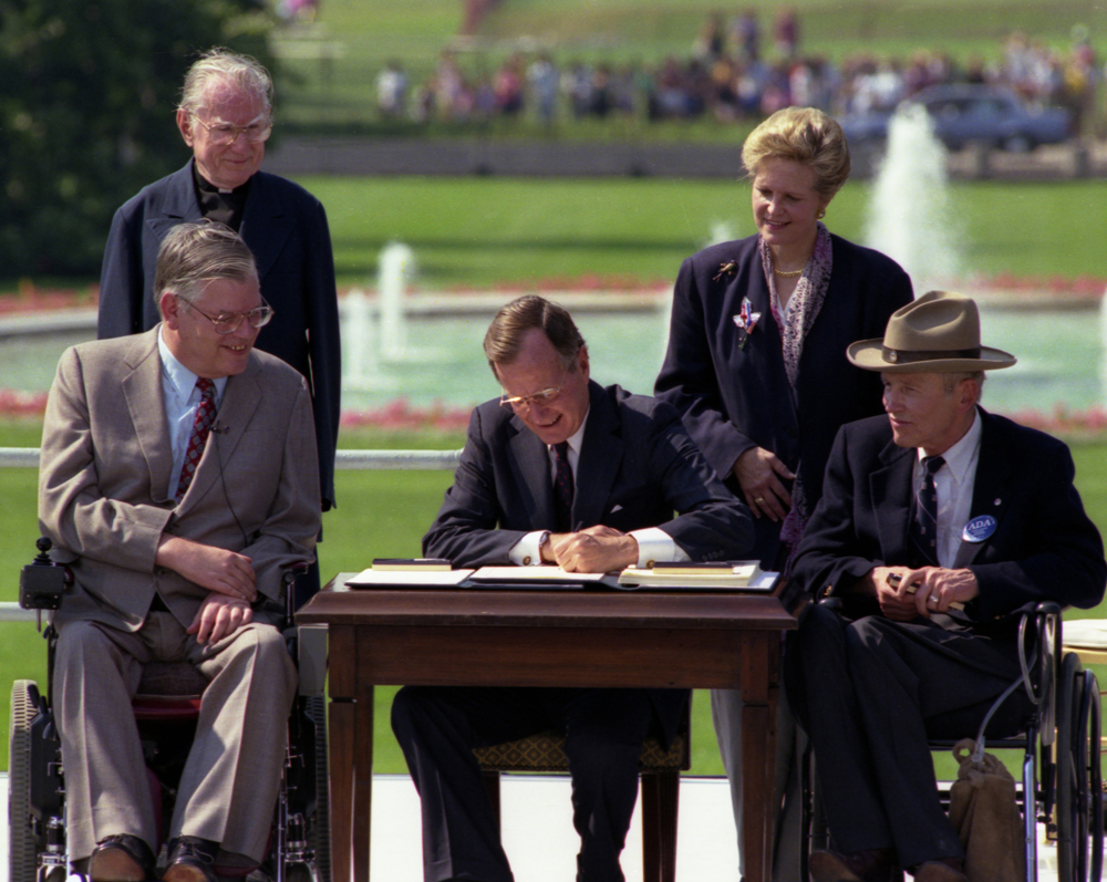 President Bush signs the Americans with Disabilities Act on the South Lawn of the White House. Sharing the dais with the President and he signs the Act are (standing left to right): Rev. Harold Wilkie of Clairmont, California; Sandra Parrino, National Council on Disability; (seated left to right): Evan Kemp, Chairman, Equal Opportunity Commission; and Justin Dart, Presidential Commission on Employment of People with Disabilities