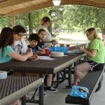 A group of women and children sit at a picnic table working on a craft project. There are craft supplies on the table.