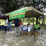 A candid shot of a pop-up tent with a green banner with text: Be Smart about Safety. There is a table set-up with paperwork and there are members of the organization sitting behind the table to answer questions.