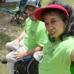 A woman with a red visor and a man sitting in a wheelchair look at the camera smiling. They both have on the green ADA25 Celebration shirts.