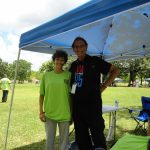 A posed shot of Tom Olin in his black ADA25 tshirt next to a young woman wearing a green ADA25 Celebration shirt. They are both standing under a blue pop-up tent.