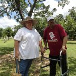 A quick posed shot of a woman in a white shirt and straw hat next to an older man using a walker in a dark red shirt and white baseball cap.