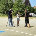 A woman stands to the left, holding a microphone as she speaks to Tom Olin in his ADA25 tshirt. A camera man is to the left filming both of them.