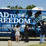 A woman stands to the left, her back to the camera as she speaks to Tom Olin in his ADA25 tshirt. A camera man is to the right filming both of them. They Road to Freedom bus is the backdrop for their conversation.