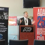 """A man stands at a podium with a microphone. Both hands are in motion as he speaks. On either side of him are the ADA25 anniversary roll-up banner and the """"celebrate"""" anniversary roll-up banner."""