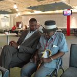 Two men sit in a common area. The one on the left is looking at the older gentleman sitting to his right who is wearing a hat and holding a cane.