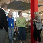 A group of three women and one man stand in a common area talking to each other.
