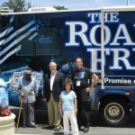 A group of five people stand at the back end of the Road to Freedom Bus posing for a photo. There are three men and two women in the group.