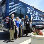 A group of four people stand at the back end of the Road to Freedom Bus posing for a photo. There are three men and one woman in the group.