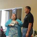 In the show room of Georgia Carolina Mobility, a female member of the Walton Options team presents an award to the male owner of the business.