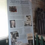 A roll-up banner with information about the History of Self-Advocacy. There is text along with images/illustrations of historical figures and places relating to Civil Rights and Independent Living.