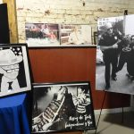A variety of images from the Disabilities rights movement including a large format black and white photo of two police officers arresting a protester, a black and white sketch of Justin Dart, a black and white photo pf Ed Roberts in his wheelchair and two color photos of persons in wheelchairs in working environments.