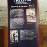 A roll-up banner with information about the Road to the ADA. There is text along with black and white images during the disability rights movement leading up to the signing of the ADA.