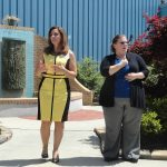 Two women stand outside in a courtyard. The woman on the left in a yellow and black dress is speaking while the woman on the right in a blue top and black sweater is using her hands for ASL interpretation.