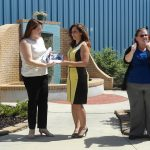 Three women are in a courtyard with a fountain behing them. The woman on the left in a white top presents an award to a woman in a yellow and black dress. The third woman in a blue top and black sweater is off to the right using her hands to use ASL to interpret the presentation.