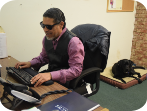 A man sits at his desk with his hands on the keyboard. He is blind and utilizing the keyboard to navigate his computer. His seeing eye dog rests on a pillow bed behind him.