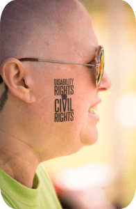Close-up of a woman's cheek with a tattoo that readers: Disability Rights are Civil Rights