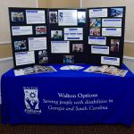 The Walton Options display showcasing the variety of services that we offer. The table top display sits on a blue table cloth with the Walton Options logo on the front.