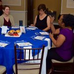 Guests mingle prior to the start of the MVP Community Awards celebration Brunch. Three women sit at a table - the one of the right is signing to the woman sitting across from her. The third woman is looking down reading her program.