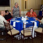 Guests mingle prior to the start of the MVP Community Awards celebration Brunch. Five people sit around a reserved table. THe man on the far left is sitting in his wheelchair while two women sit next to him. A third woman is standing and a man sits on the far right with sunglasses. They all appear to be talking and laughing.