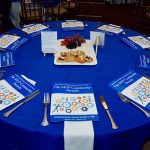 An image of the guest tables including programs placed at each seat with a white napkin and silverware. In the middle of the table is a white tray with pastries and fruit. The table cloth is dark blue.