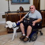 A man and his service dog start to leave the front desk counter after checking in at the Brunch. The man is using an electronic wheelchair.