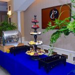 Prior to the Ceremony, guests enjoyed a brunch buffet at the Legends Club. A table with a tiered tower of fruit and quiche is set-up next to other serving trays that have not had food placed in them yet.