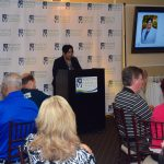 We were honored to have Kellie Irving, the City of Augusta Compliance Department Director, as our guest speaker. She spoke about working towards an inclusive community in Augusta. Kellie is standing at the podium, speaking into the microphone. The Walton Options backdrop is behind her and to the right a TV screen displays a headshot of Kellie and her credentials. Guests sitting at their table can also be seen in the foreground.