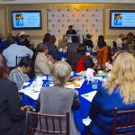 A photo of Kellie Irving presenting her speech during our ceremony with multiple, full tables of guests listening.