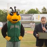 On the baseball field, Commission Sean Frampton reads the City of Augusta Proclamation honoring the 25th Anniversary of the ADA. Next to him, Auggie, the GreenJackets' mascot stands.
