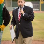 On the baseball field, Commission Sean Frampton speaks into a microphone to the crowd. Next to him, Auggie, the GreenJackets' mascot stands.