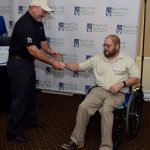 A representative from Adaptive Driving Solutions accepts the Inclusive Employment Award from Robbie Breshears from our SC Office. A man stands on the left reaching out to accept the award while Robbie on the right reaches up to shake his hand. Robbie is sitting in his wheelchair.