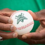 One of Walton Options' very own, Willie Jones, was honored to throw out a first pitch, recognizing the ADA's 25th anniversary. This is a close up of Willie's hands holding a baseball with the GreenJackets logo on it.