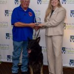 Veterans K9 Solutions' representative poses with our SC Director Cyndy Anzek after receiving the Outstanding Service Organization Award. A man stands on the left holding the award over his service dog while Cyndy stands to the right. They are both looking at the camera smiling.