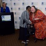 Executive Director Tiffany Clifford presents Ms. Lura the Walton Options Dedicated Volunteer award. Host Barclay Bishop is to the far right behind the podium with the Walton Options logo. Ms. Lura is in the middle giving Tiffany a kiss on the cheek as Tiffany is handing her the award.