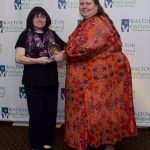 The Winner of the Walton Options MVP Awards accepts her awards from Executive Director Tiffany Clifford. The two women are standing in front of the Walton Options backdrop. Tiffany is on the right and Carolyn is on the left.