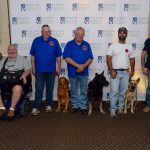 Members of K9 Solutions pose in front of the Walton Options back-drop to commemorate the Ceremony. The man on the far right sits in his electronic wheelchair. Next to him are four other men, each with their service dog to the right of them.