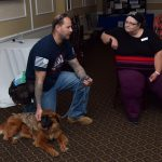 A man kneels next to his service dog to speak with a woman sitting at a table. He is petting his service dog while he talks.