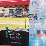 A candid shot of the Walton Foundation for Independence table - a table with a black table cloth and paperwork sitting on it. A Walton Foundation roll-up banner is next to the table. They are under a red, pop-up tent.