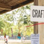 """A """"Crafts"""" sign is posted on the post of an outdoor picnic area with some painting graphics strung up below the sign."""