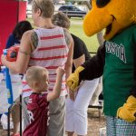 A candid shot of a smiling young boy giving Auggie, the GreenJackets stylized Yellow jacket mascot, a fist pump.
